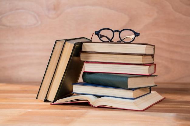 テーブルの上に眼鏡を持つ様々な本