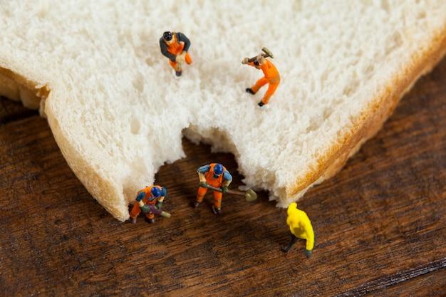 上の作業ミニチュア労働者がパンをスライスしました