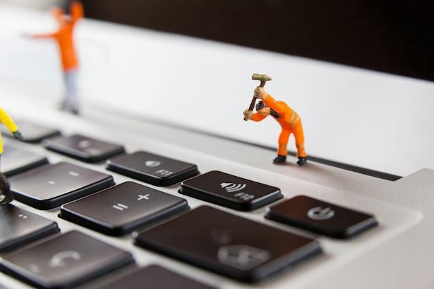 ノートパソコンのキーボードを修復ミニチュア労働者