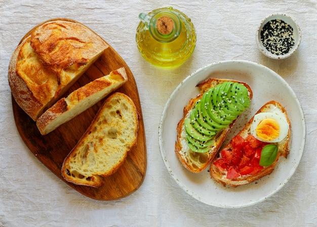 Бутерброды из пшеничного хлеба с авокадо, яйцом, помидором