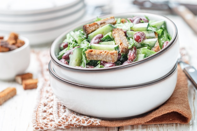 Салат из фасоли, огурцов, салата и сухариков