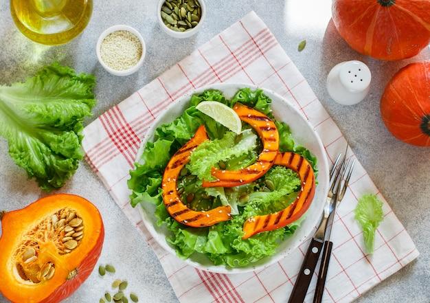 Вкусный легкий салат из жареных ломтиков тыквы и салата с кунжутом, лимонным соком и оливковым маслом