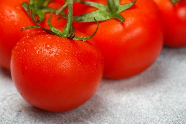 枝に水滴と新鮮なジューシーな完熟トマト