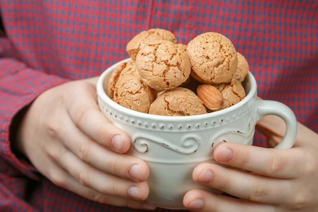子供はイタリアのアーモンドクッキーアマレッティとカップを保持しています。クリスピービスケット。