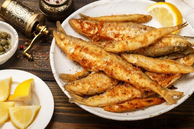 白いプレートで揚げたワカサギ、小魚、ケッパー、レモン、コショウ、木製のテーブルの塩、素朴なスタイルの美味しいディナー