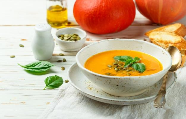 オリーブオイル、種子、バジルを使った食事ベジタリアンカボチャクリームスープのピューレ