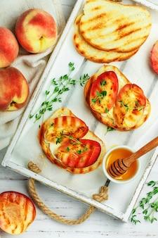 Летний завтрак для гурманов - бутерброды (хлебные тосты, брускетта) с жареными персиками, сливочным сыром