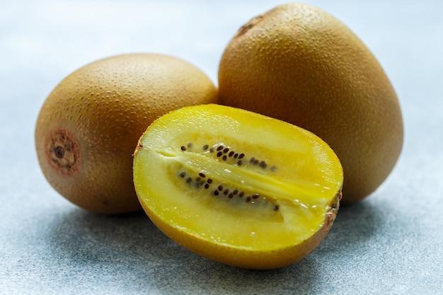 黄金の有機キウイ、全体とグレーの熟したジューシーなフルーツ
