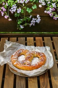 シナモンシュガーソフトプレッツェル、ストリートカフェの木製テーブル、お茶やコーヒーのスナック