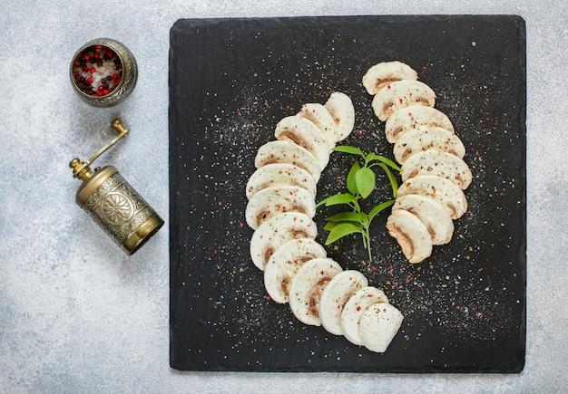 新鮮なキノコシャンピニオンのカルパッチョ、マッシュルームスライスのペッパーと塩の前菜