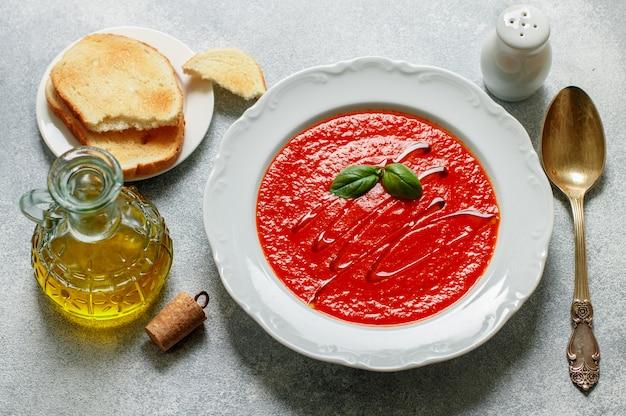 白い皿にバジルとスパイスのトマトスープ。パントーストとオリーブオイルを添えたボリュームのあるボリュームたっぷりの料理。