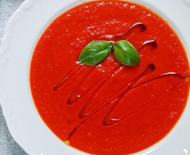 白いプレートのクローズアップでバジル、スパイス、オリーブオイルとトマトのスープ。