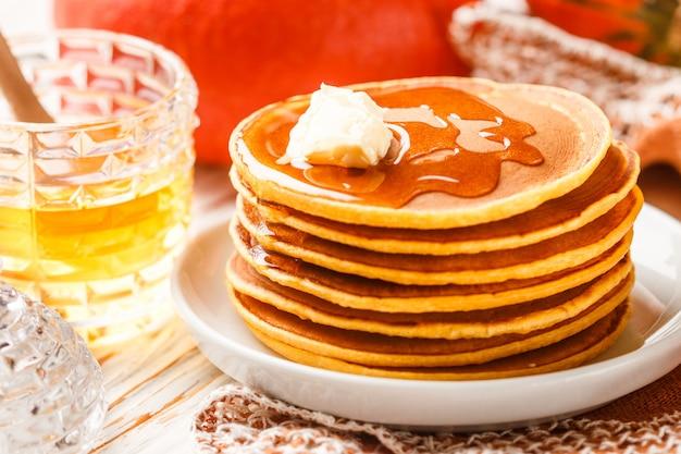 白いプレートに蜂蜜とバターと新鮮な自家製パンプキンパンケーキ。おいしい伝統的な健康的な朝食