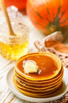 白いプレートに蜂蜜とバターと新鮮な自家製パンプキンパンケーキ