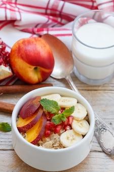 健康的な朝食。バナナ、ピーチ、ネクタリン、ザクロ入りのオートミール、シナモン入り