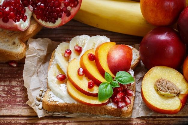 健康的な朝食。デザート。クリームチーズ、バナナ、桃、ネクタリン、ザクロのトースト