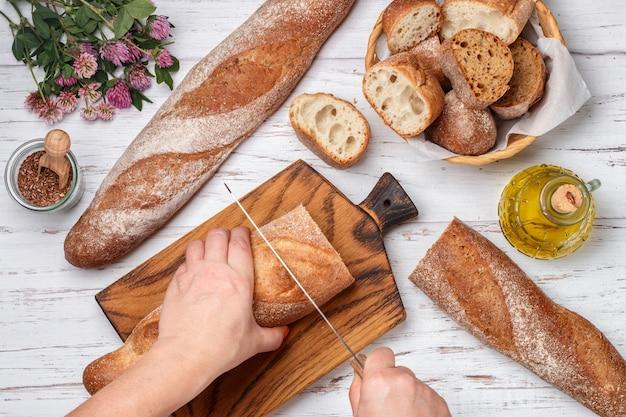 女性は焼きたてのパンを切る