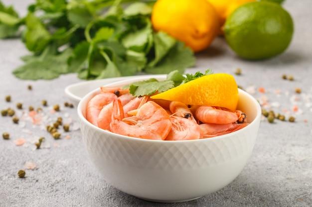 Креветки креветки с лимоном, кинзой и соевым соусом в белой тарелке, морепродукты,