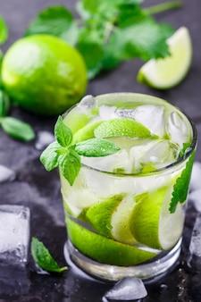 暗い石の背景、モヒートのグラスにライム、ミント、アイスキューブと冷たいさわやかな夏の飲み物
