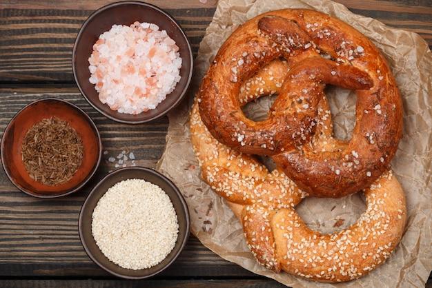 Крендель с тмином, кунжутом и крупной солью на темном деревянном столе