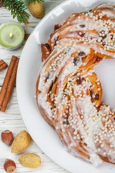 クリスマス(新年)パイ、シナモン、アーモンド、ヘーゼルナッツ、乾燥クランベリーをクローズアップ。粉砂糖で覆われたロールクランチ