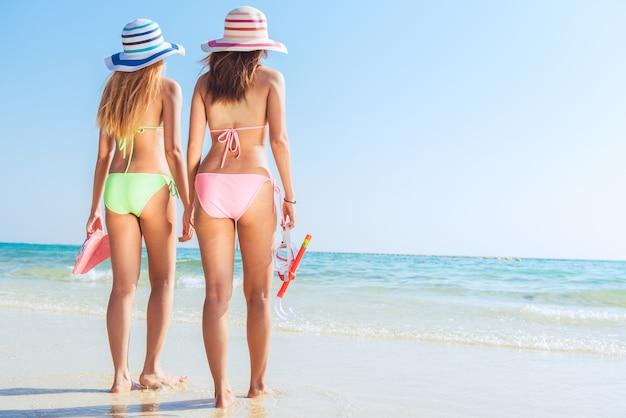 ビーチの休暇のシュノーケルの女の子マスクとフィンでシュノーケリング。ビキニの女性は、夏の熱帯の休暇でリラックスして、シュノーケル・チューバとフリッパーズ・サン・タンニングでシュノーケリング活動を行っています。サンタンのボディケア。