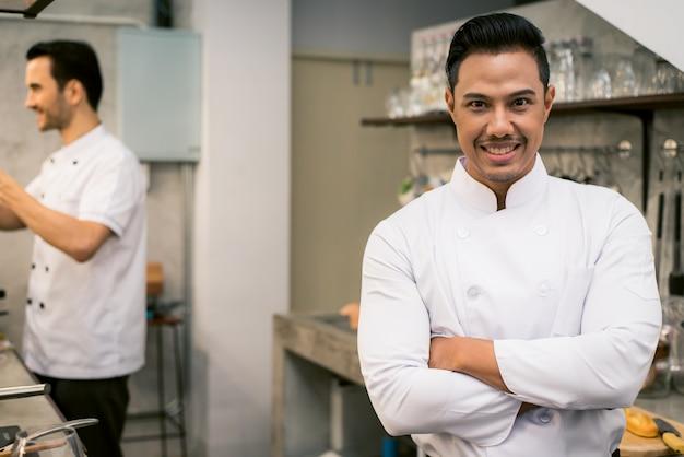 レストランのキッチンインテリアで若いアジアのシェフを笑顔にしています。ヴィンテージフィルター画像。