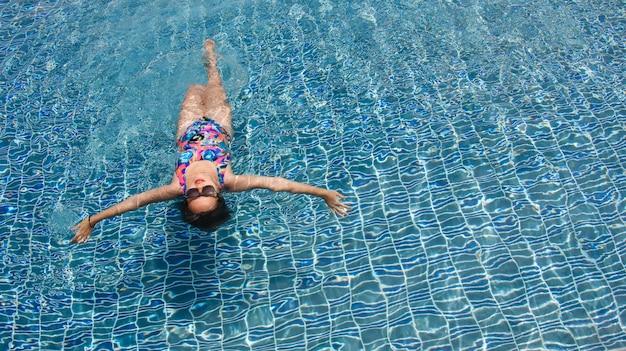 水晶のような水の上に広い腕を開けてプールをリラックスさせて泳ぐ女性のリアビュー。