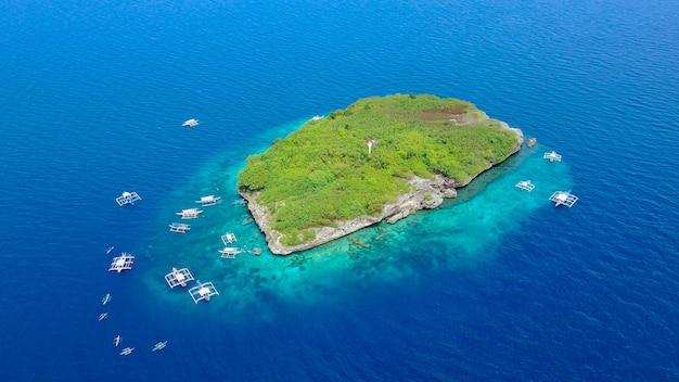 Вид с воздуха на песчаный пляж с туристами, плавающими в красивой чистой морской воде пляжа сумилонского острова, приземляющегося возле ослоба, себу, филиппины. - увеличьте цвет обработки.