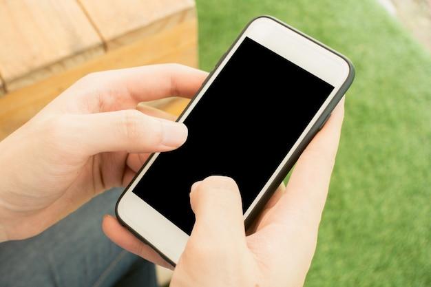 電話でクローズアップ手のタッチぼやけた自然の背景にモバイルの空白の黒い画面のアウトドアライフスタイルのコンセプト - モックアップ画像を使用することができます。ヴィンテージエフェクトスタイルの写真。