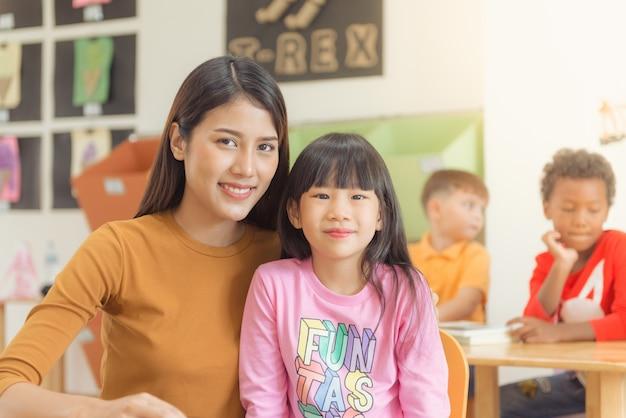 教師と学習して楽しむ授業中の小学生のグループ。ヴィンテージエフェクトスタイルの写真。