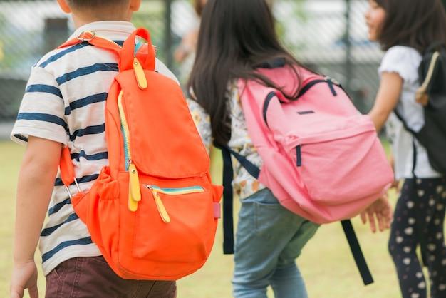 Три ученика начальной школы идут рука об руку. мальчик и девочка со школьными сундуками за спиной. начало школьных занятий. теплый день осени. обратно в школу. маленькие первоклассники.