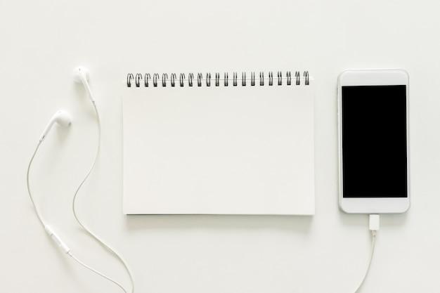 Минимальное рабочее пространство - творческая квартира лежал фото рабочего стола стол с альбом и мобильный телефон с пустой экран на фоне копирования пространства на белом фоне. вид сверху, плоская фотография.