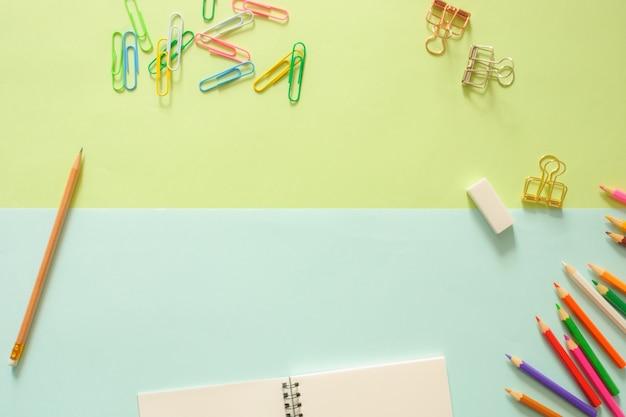 最小限の作業スペース - スケッチブックとコピースペースに木製の鉛筆でワークスペースデスクの創造的な平らなレイアウトの写真緑色と青色のパステルの背景。トップビュー、フラットレイ写真。