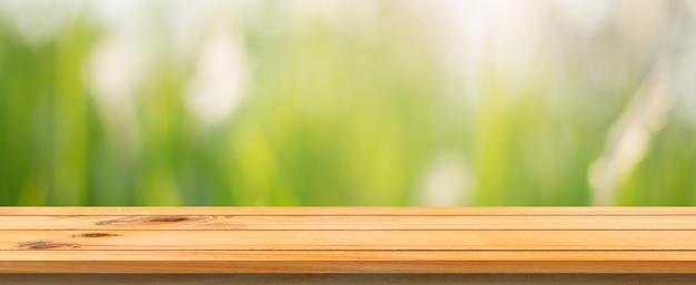 木製のボードの空の表の背景をぼかした。ぼかし木の森の背景の上に展望茶色の木製のテーブル - あなたの製品を表示またはモンタージュのためにモックアップすることができます。春の季節。パノラマバナー