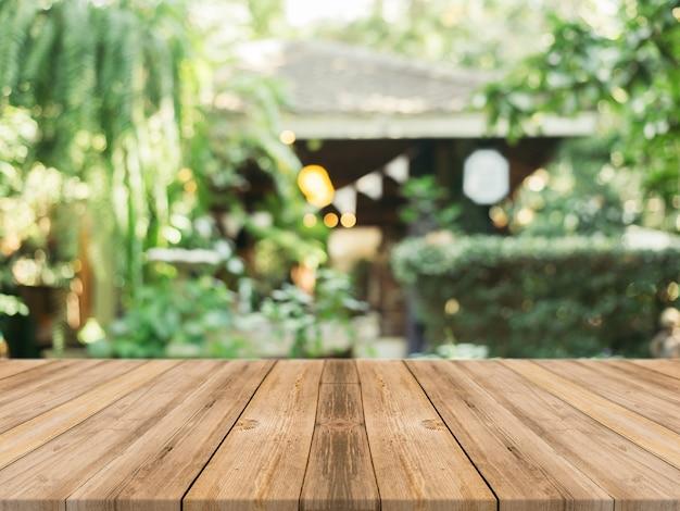 ぼんやりした背景の前に木製ボードの空のテーブル。コーヒーショップでのぼかしを越える茶色の木目の展望 - あなたの製品を表示またはモンタージュするために使用することができます。製品の表示のためにモックアップします。