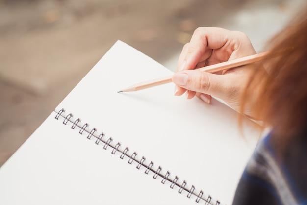 さまざまな項目と木製の机に置かれた螺旋メモ帳で書く女性の手のクローズアップ。ヴィンテージエフェクトスタイルの写真。