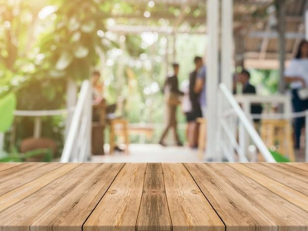 ぼんやりした背景の前に木製ボードの空のテーブル。コーヒーショップでのぼかしを越える茶色の木目の展望 - あなたの製品を表示したり、モンタージュするために使用することができます。製品の表示のためにモックアップしてください。