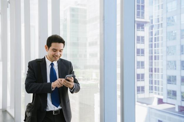 スマートフォンの男 - 空港の若い実業家。スマートフォンを使用してカジュアルな都市のプロのビジネスマンは、オフィスビル内で幸せに笑顔。屋内でスーツジャケットを着ているハンサムな男。