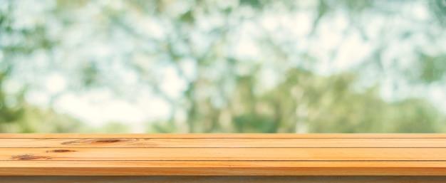 木製のボードの空の表の背景をぼかした。ぼかし木の森の背景の上に玄関茶色の木製のテーブル - あなたの製品を表示またはモンタージュのためにモックアップすることができます。春の季節。パノラマバナー