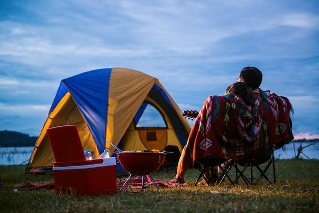 Палатка беззаботная пара расслабляющий дистанционного концепции путешествия - романтические азиатские пары туристов, сидя у костра возле палатки, обнимая друг друга под деревьями и ночное небо. ночной кемпинг