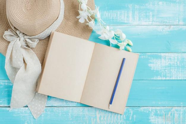 休暇の概念。開いた本、青い木製のテーブルにタオルと帽子の山。青い木製の床に夏のアクセサリー。トップビューとコピースペース、美しい。モックアップとファッションと美しさ。