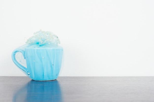グランジの背景上に木製のテーブル上の青いマグカップ。木製ボード上のカラフルなスタックコーヒーカップ。ヴィンテージレトロエフェクトスタイルの写真。