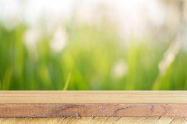 ぼんやりした背景の前に木製ボードの空のテーブル。森の中のぼやけた木々の上に見える茶色の木材 - 製品の表示やモンタージュのためにモックアップすることができます。春の季節。ヴィンテージフィルター。