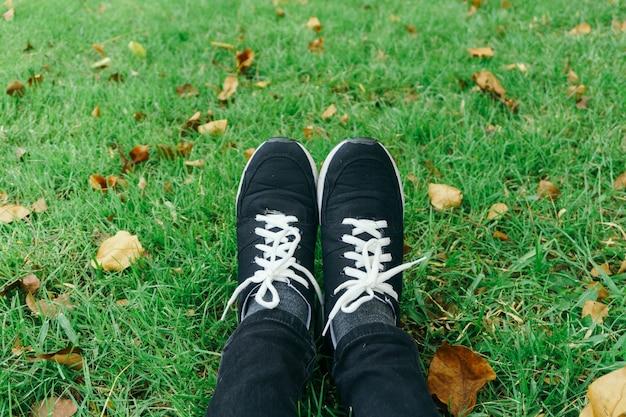 晴れの穏やかな夏の日に芝生の上の少女の足に若者のスニーカー。