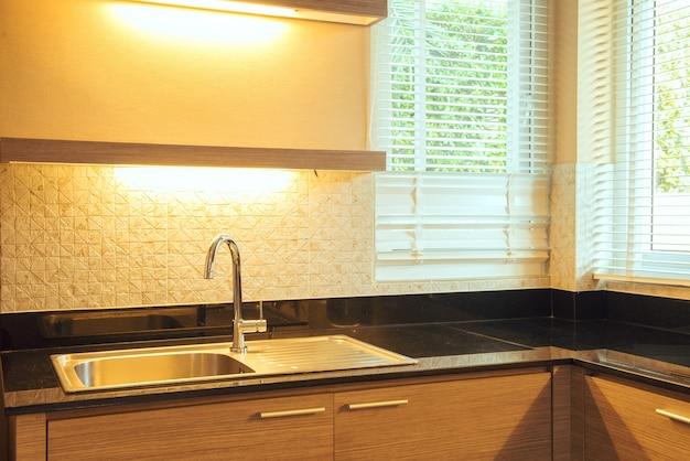 現代の白い台所のシンク、朝の太陽の光線