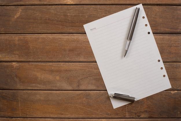 オフィスの木製のテーブルにペンでメモ帳。