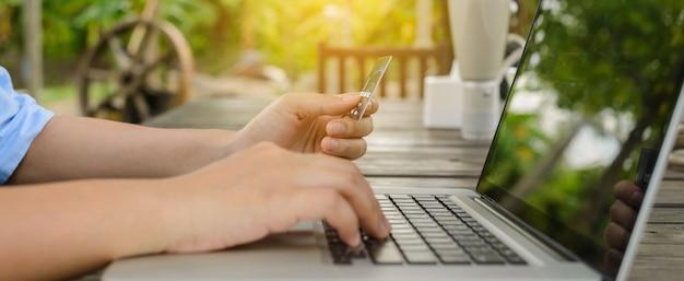 Женщина, держащая кредитную карту в руке и вводя код безопасности, используя ноутбук