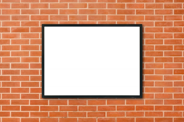 部屋の赤レンガの壁の背景にぶら下がって空のポスターの額縁をモックアップ