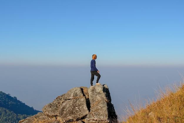 タイのカラフルな夏の山々で素晴らしい風景を見ている丘の上の男